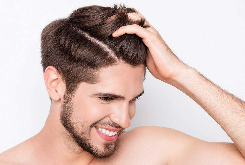 Stock image of a male model holding hair with left hand smiling and feeling confident